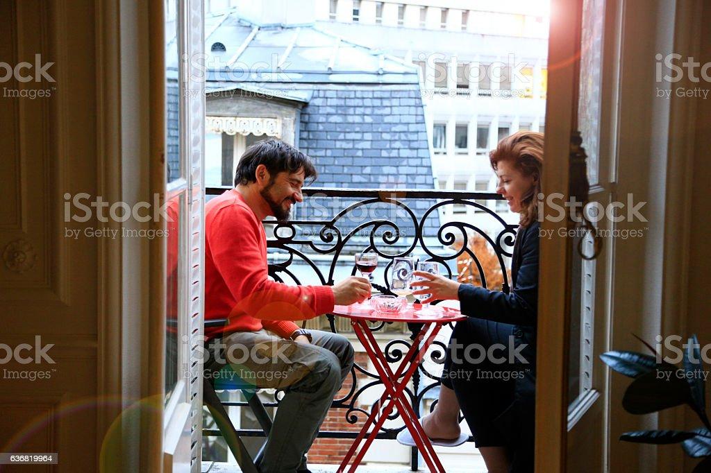 Loving couple having drink on a balcony in Paris stock photo
