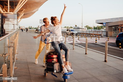 Joyful man is pushing trolley with baggage and his girlfriend on their way to airport. Website banner