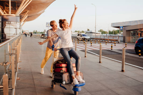 Loving couple having fun before going on trip stock photo Joyful man is pushing trolley with baggage and his girlfriend on their way to airport. Website banner travel stock pictures, royalty-free photos & images