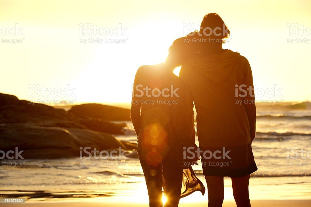 Loving couple holding hands at the beach watching the sunset stock photo