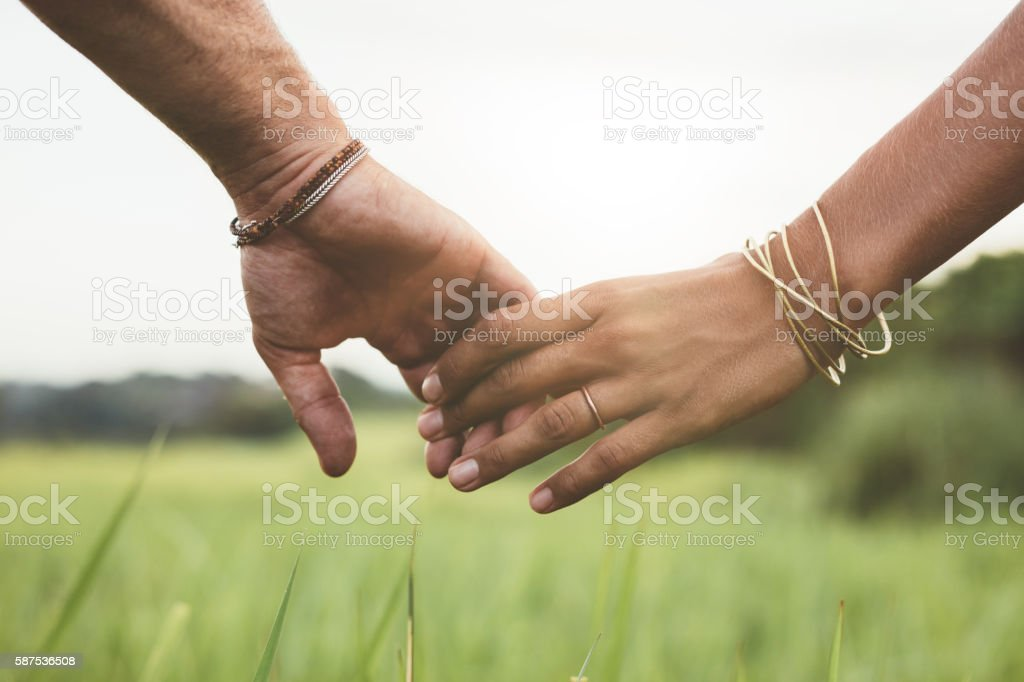 Loving couple holding hands in a field stock photo