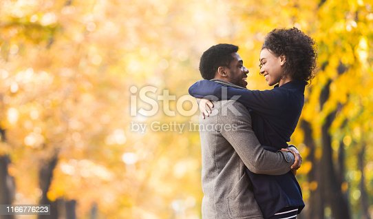 Loving couple hugging and looking into each other eyes in autumn city park, copy space