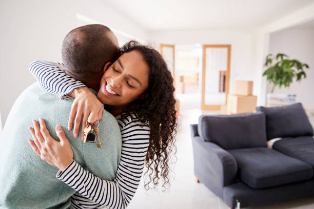 loving couple hugging holding keys to new home on moving day - buy a house key imagens e fotografias de stock