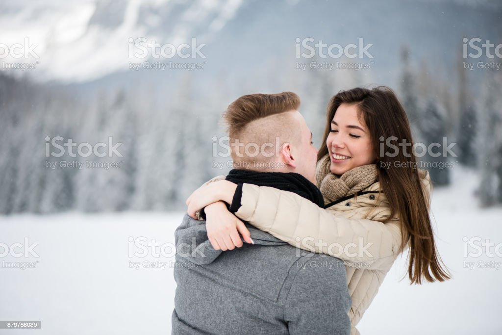 Loving couple hugging in snow stock photo
