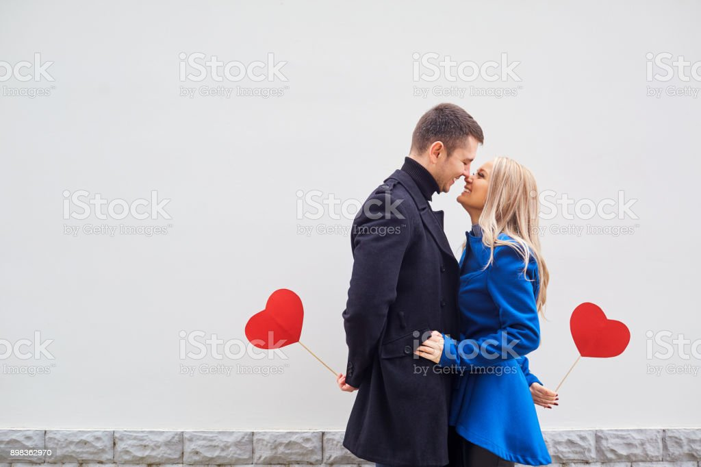 A loving couple in a coat with hearts in hands. stock photo