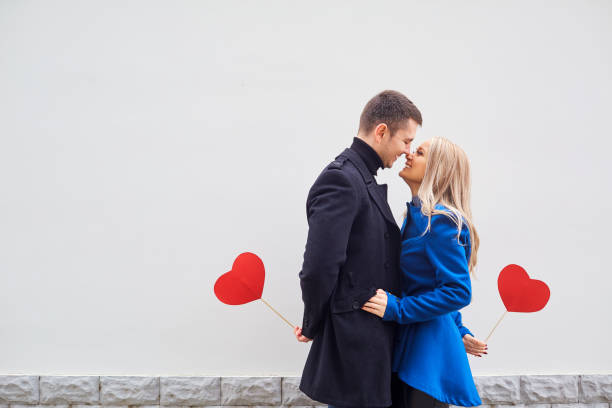 a loving couple in a coat with hearts in hands. - falling in love stock pictures, royalty-free photos & images