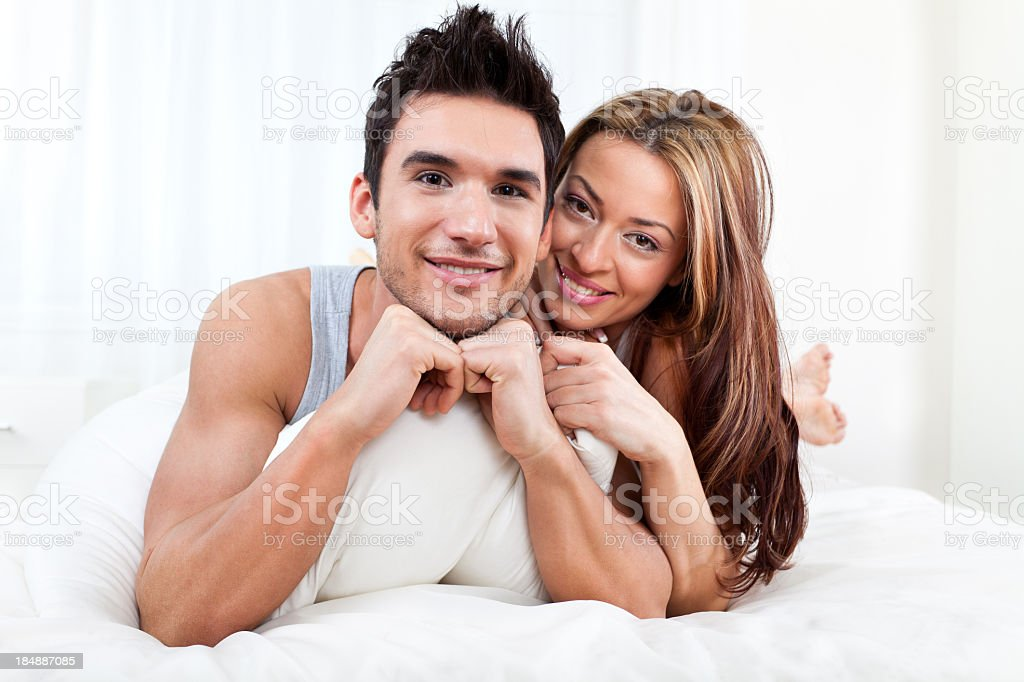 Loving couple in bed looking at camera royalty-free stock photo
