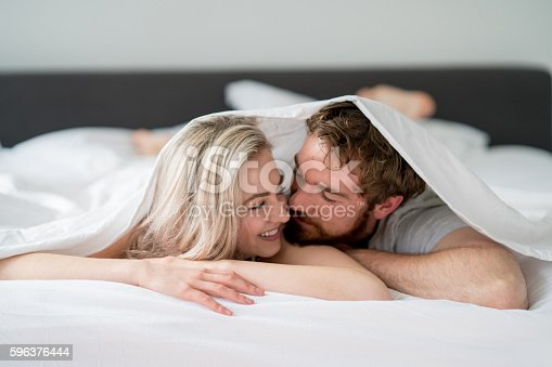 504371332istockphoto Loving couple in bed 596376444