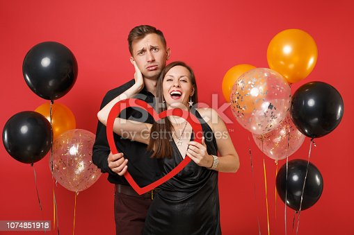 istock Loving couple in black clothes hold heart celebrating birthday holiday party isolated on bright red background air balloons. St. Valentine International Women Day Happy New Year 2019 concept. Mock up. 1074851918