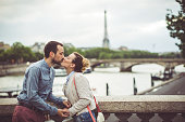 Young loving couple is kissing in Paris, France, on one of it's famous bridges, while Eiffel tower is in the background.