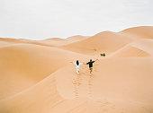 Young couple enjoying the sunset in dunes. Romantic traveler walking on the Sahara desert. Adventure travel lifestyle concept.