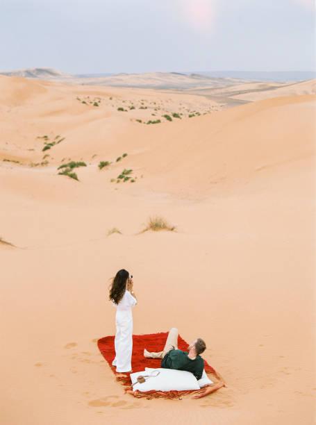liebes paar in sahara-wüste. - hochzeitsreise dubai stock-fotos und bilder