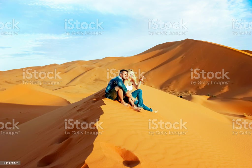 Loving couple in the Sahara Desert. Morocco. stock photo