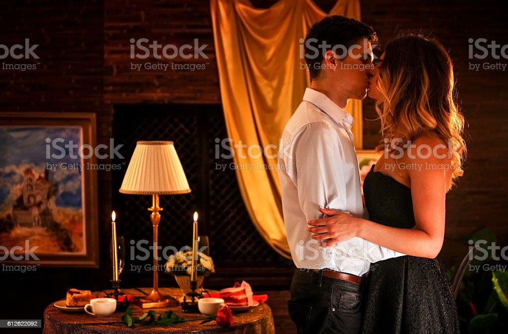 Loving couple kissing in romantic home interior. stock photo