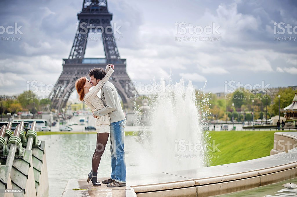 Loving couple kissing near the Eiffel Tower in Paris stock photo