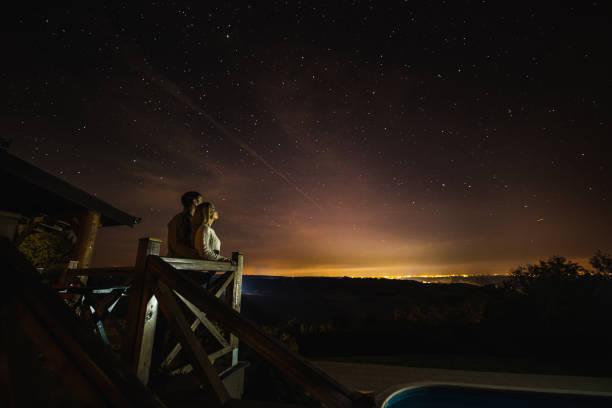 liebespaar, atemberaubenden blick auf konstellation von ihrem balkon aus zu betrachten. - romantischer abend stock-fotos und bilder