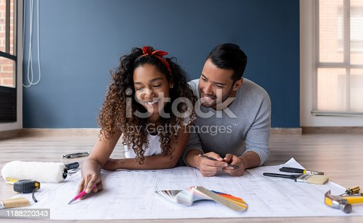 Happy loving couple looking at the blueprints of their new house while lying on the floor smiling