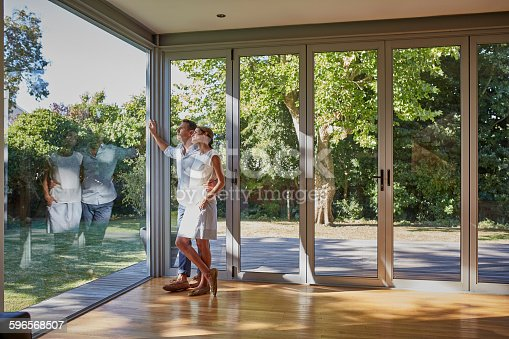 Full length of loving mid adult couple looking through glass window