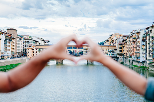 Loving couple making heart with her hands in Florence