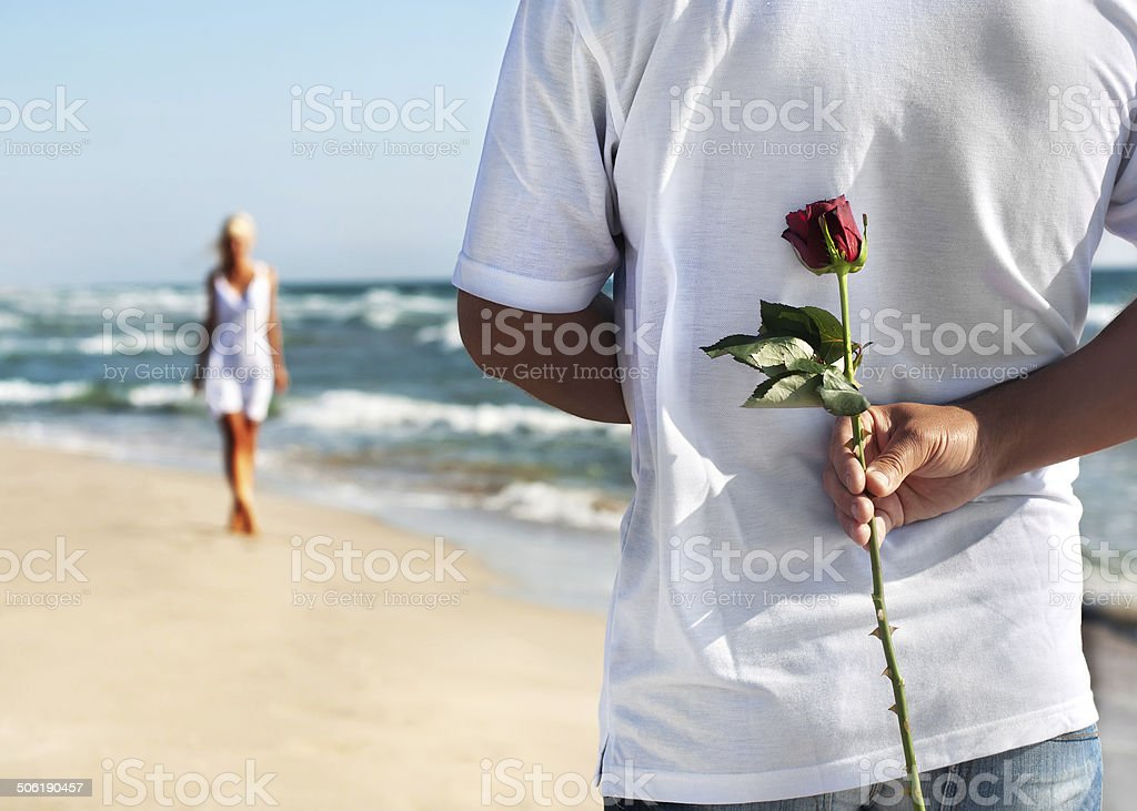 loving couple, man with rose and woman on sea beach stock photo