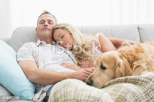 istock Loving couple napping on couch with their dog 518352269