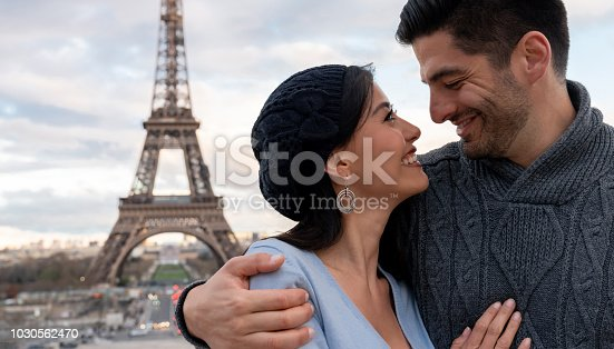 Portrait of a loving couple on a romantic getaway in Paris smiling with the Eiffel Tower at the background