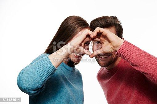 istock Loving couple peeking through heart shaped hands 621134614