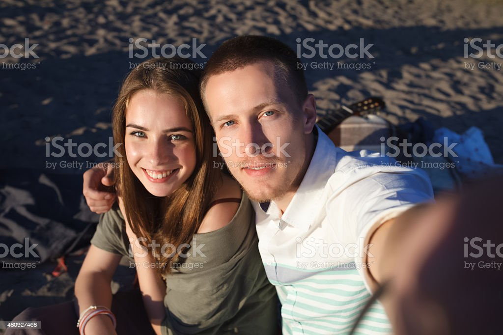 loving couple photographing themselves on the beach stock photo