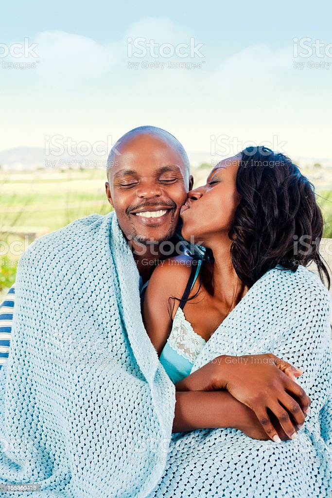 Loving couple Happy couple sitting outdoors, woman kissing her boyfriend. Adult Stock Photo