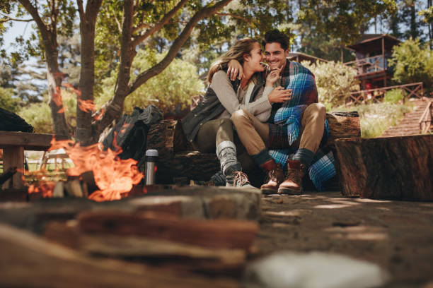 Loving couple relaxing near campfire stock photo