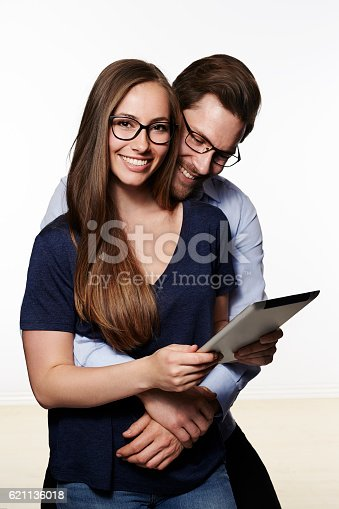 621502402 istock photo Loving couple sharing tablet, smiling 621136018