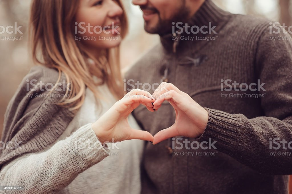 young happy loving couple showing heart for valentine day on cozy...