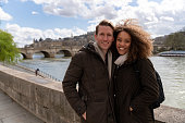 Portrait of a loving mixed-race couple sightseeing in Paris and looking at the camera smiling - people traveling concepts