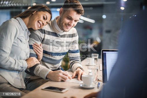 944314580 istock photo Loving couple signing a contract on a business meeting with their insurance agent. 1162282215
