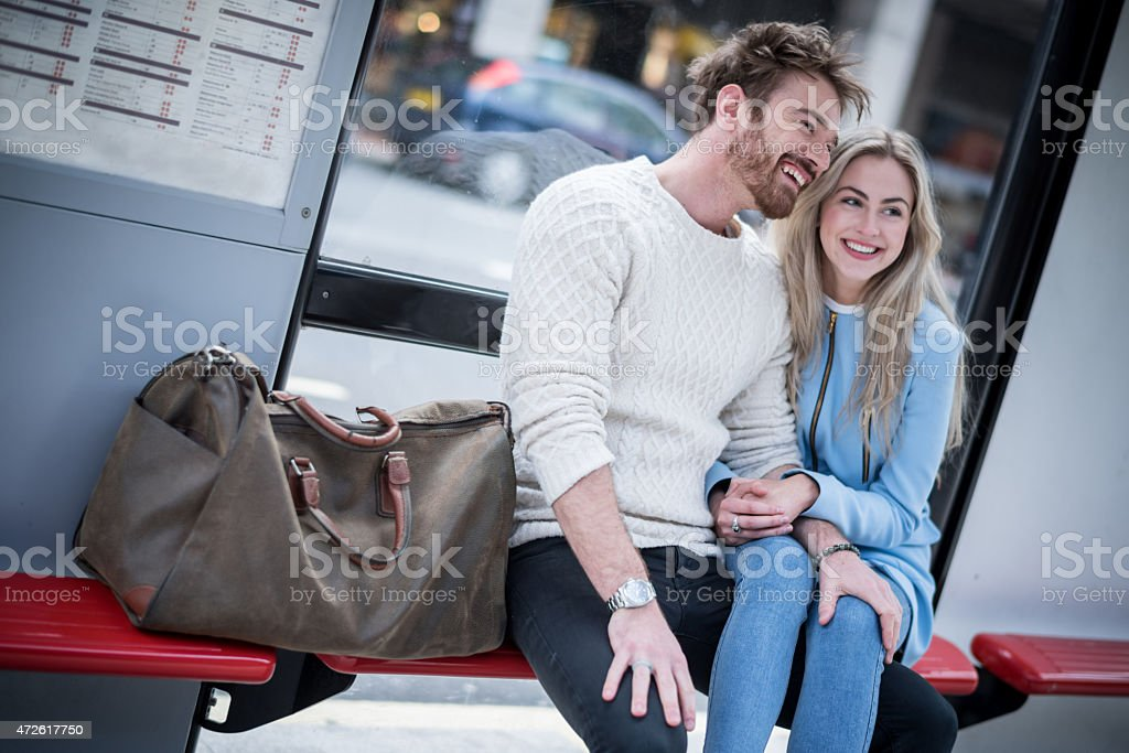 Loving couple sitting at the bus stop stock photo