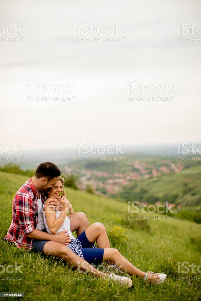 Loving couple sitting  hugged on grass in the mountain - Royalty-free Adult Stock Photo