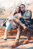 istock Loving couple sitting on the bench in the park and 637567914