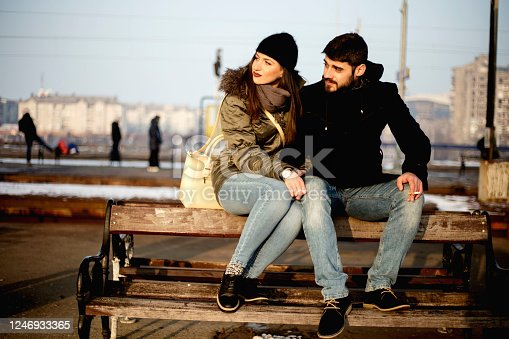 Loving couple sitting on wooden bench at train station. Couple sitting waiting for the train at platform.