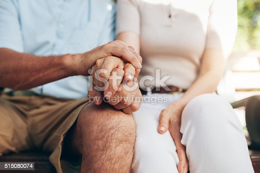 istock Loving couple sitting together and holding hands 515080074