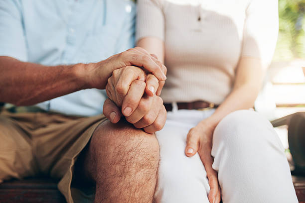Loving couple sitting together and holding hands Close up shot of senior couple holding hand. Loving couple sitting together and holding hands. Focus on hands. husband stock pictures, royalty-free photos & images
