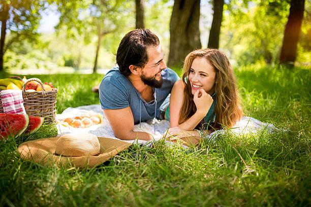 liebespaar lächeln an jeder anderen auf einer picknick-decke - romantisches picknick stock-fotos und bilder