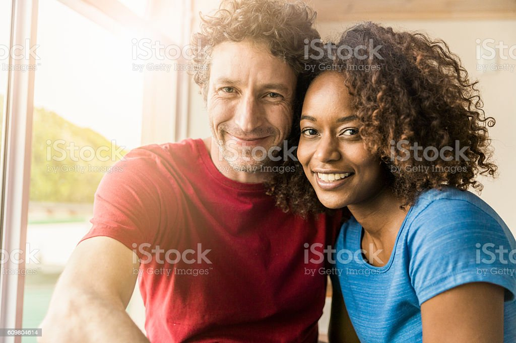 Loving couple smiling by window at home stock photo