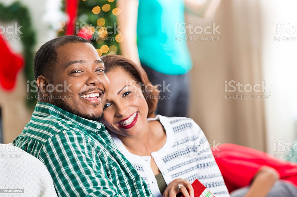 Loving couple snuggle on the couch at Christmastime stock photo
