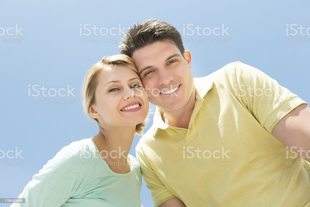 Loving Couple Standing Against Clear Blue Sky stock photo