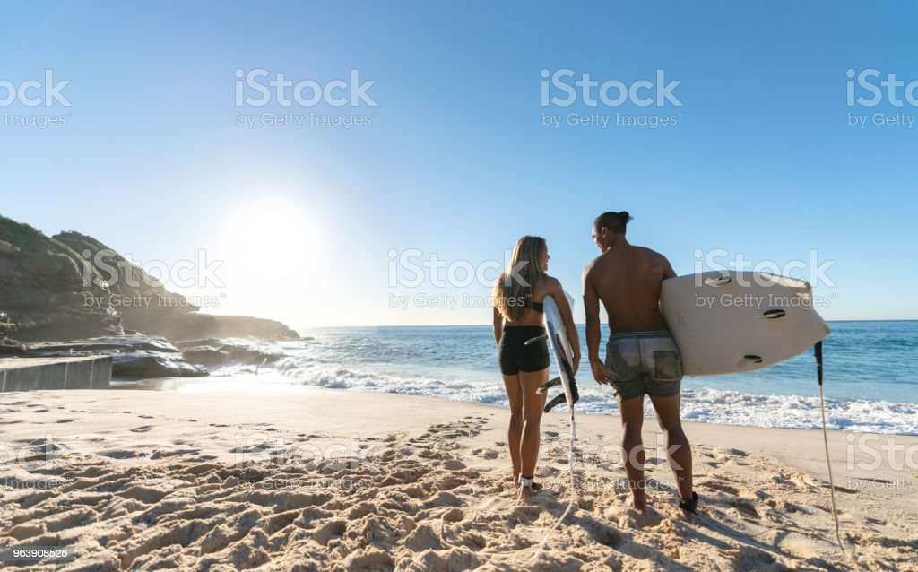 Loving couple surfing at the beach and looking happy - Royalty-free Adult Stock Photo