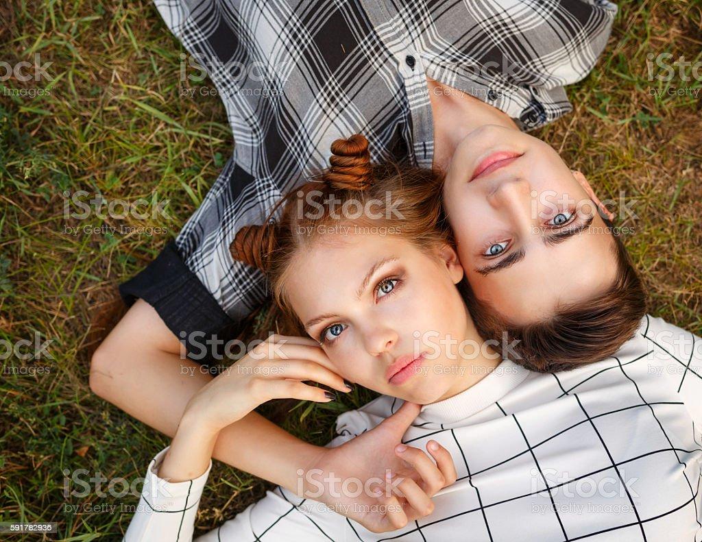 Loving couple teenagers lying on lawn. stock photo