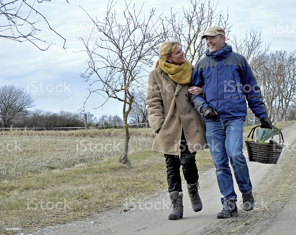 Loving couple walk arm in arm down the road royalty-free stock photo