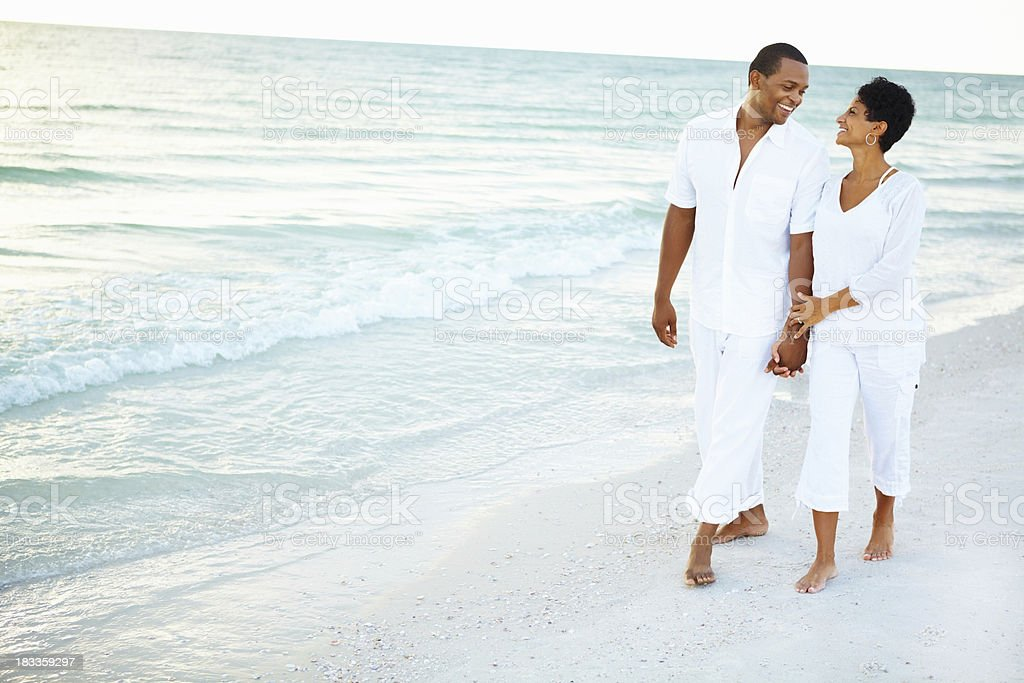 Loving couple walking along the beach stock photo