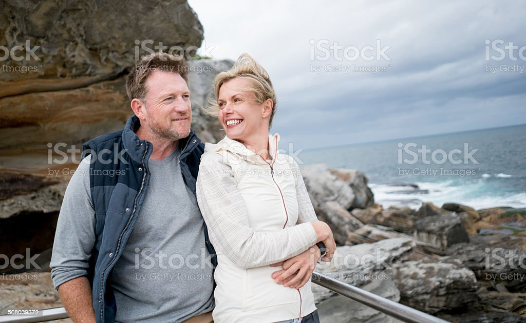 Loving couple walking by the beach stock photo