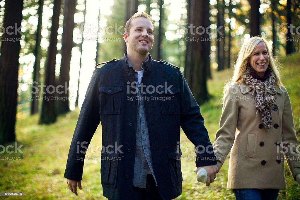 Loving Couple Walking in Sunlit Woods stock photo